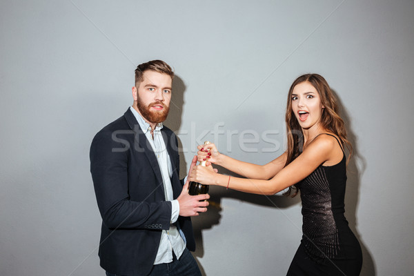 Young couple in formal wear fighting for champagne bottle Stock photo © deandrobot