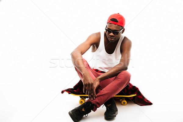 Vonzó afrikai férfi sapka napszemüveg ül Stock fotó © deandrobot