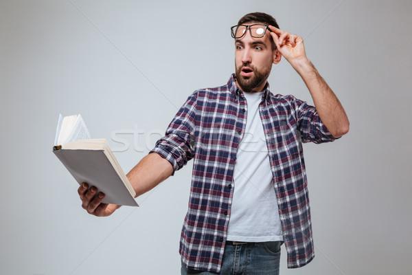 Shocked Bearded man in eyeglases reading book Stock photo © deandrobot