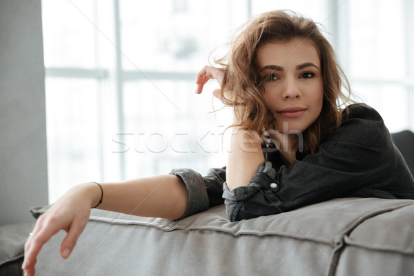Young incredible woman sitting at home indoors Stock photo © deandrobot