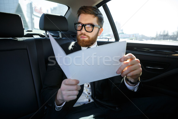 Businessman with documents driving on car back seat Stock photo © deandrobot