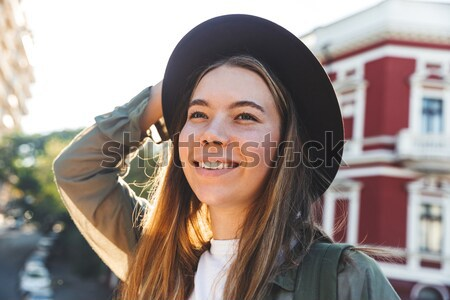 Pretty Woman in warm clothes listening music on the street Stock photo © deandrobot