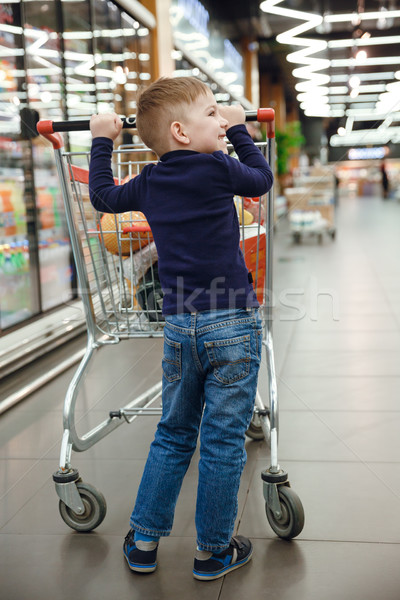 Vertical image of smiling boy with shopping trolley Stock photo © deandrobot