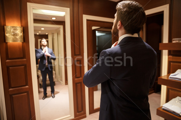Backview image of man in suit near mirror Stock photo © deandrobot