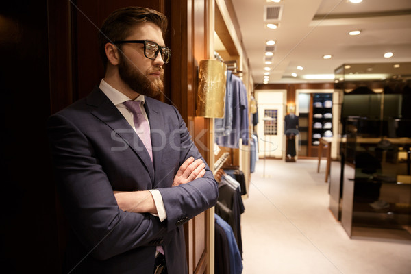 Concentrated young bearded businessman standing indoors Stock photo © deandrobot