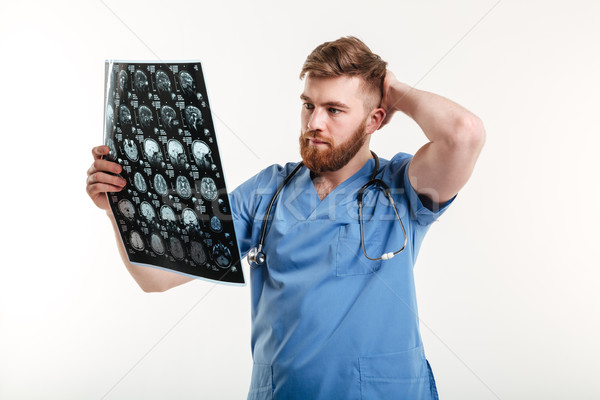 Portrait of a young medical doctor analyzing CT scan Stock photo © deandrobot