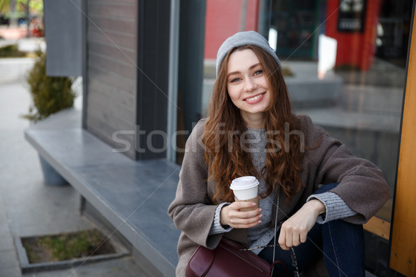 Stock photo: Cheerful woman sitting and drinking coffee-to-go in the city