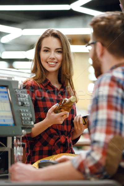 Smiling young lady near cashier's desk. Stock photo © deandrobot