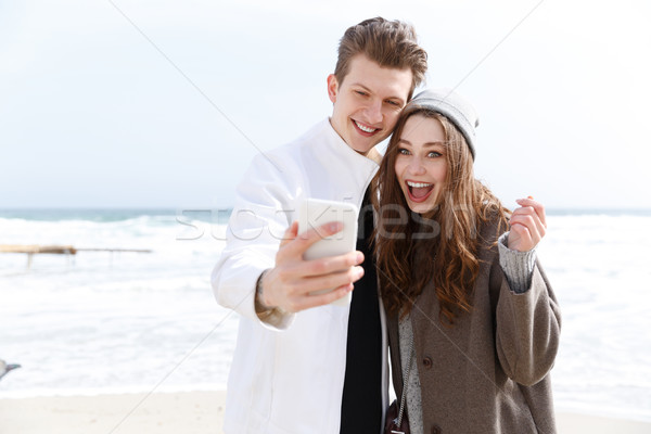 Happy young couple taking selfie with cell phone outdoors Stock photo © deandrobot