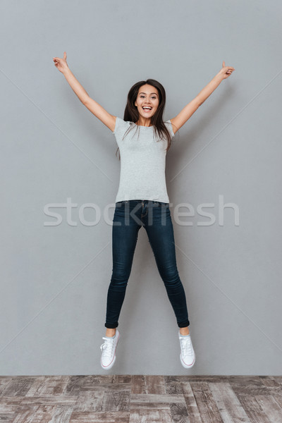 Feliz mulher jovem as mãos levantadas saltando ar Foto stock © deandrobot