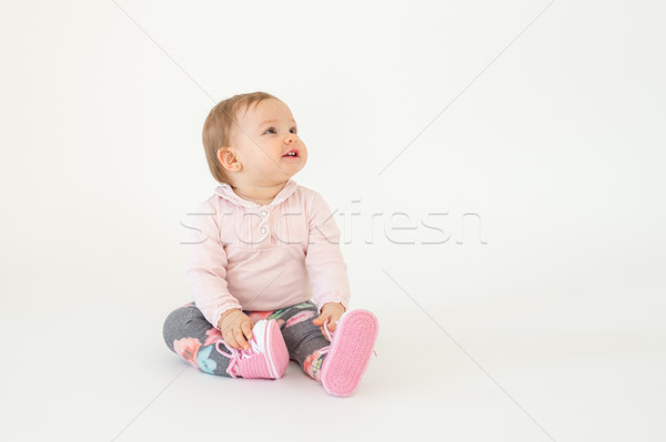 Cute little baby girl sitting on floor isolated Stock photo © deandrobot