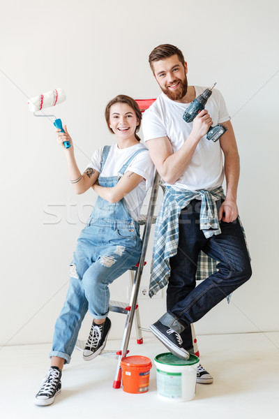 Cheerful lovers looking camera while sitting on ladder isolated Stock photo © deandrobot