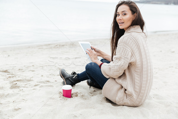 Beautiful young caucasian lady sitting outdoors at beach Stock photo © deandrobot