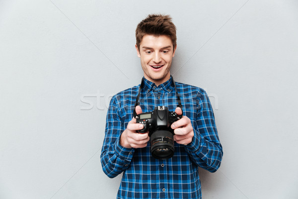 Man looking at images on camera and surprising Stock photo © deandrobot