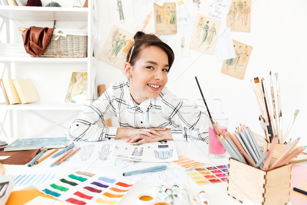 Happy woman fashion illustrator sitting at the table Stock photo © deandrobot
