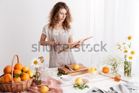 Stock photo: Woman standing indoors near table with a lot of citruses