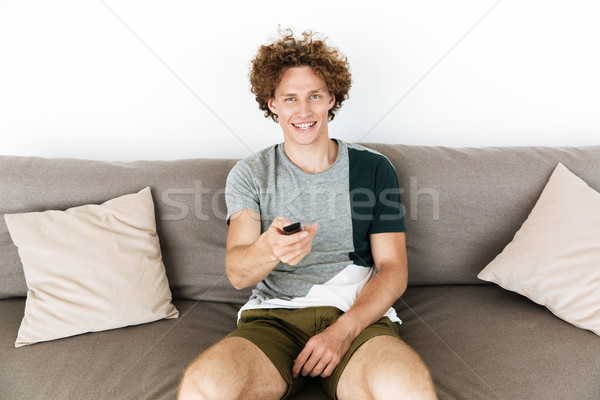 Handsome cheerful man sitting on sofa holding remote control Stock photo © deandrobot