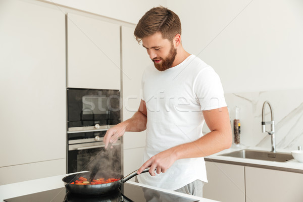 Side view of pleased bearded man cooking Stock photo © deandrobot