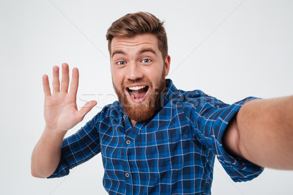 Happy bearded man making selfie and giving five at camera Stock photo © deandrobot