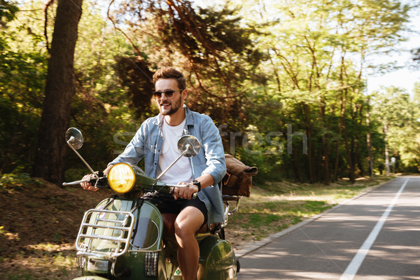 Serious young bearded man on scooter outdoors. Stock photo © deandrobot