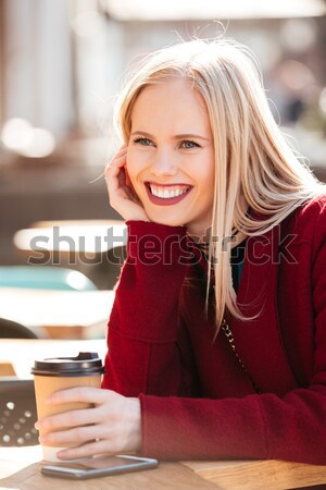 Smiling young caucasian woman sitting in cafe outdoors chatting. Stock photo © deandrobot