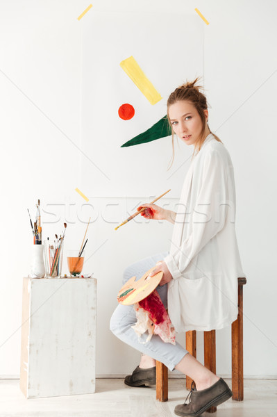 Concentrated young caucasian lady painter Stock photo © deandrobot