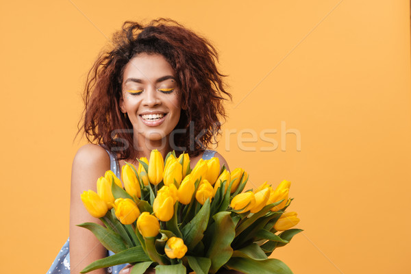 Mosolyog afrikai nő csukott szemmel tart virágcsokor Stock fotó © deandrobot