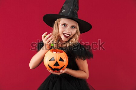 Smiling woman in halloween costume holding curved pumpkin Stock photo © deandrobot