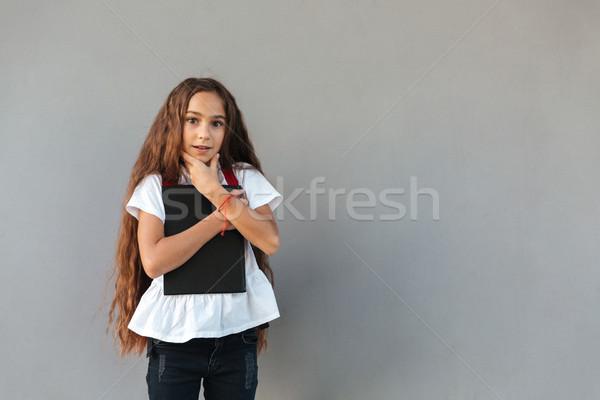 étonné brunette écolière cheveux longs livre Photo stock © deandrobot
