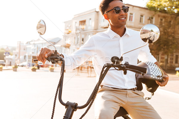 Happy african man sitting on modern motorbike outdoors Stock photo © deandrobot