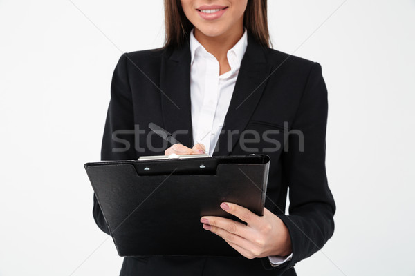 Cropped photo of cheerful business woman holding clipboard. Stock photo © deandrobot