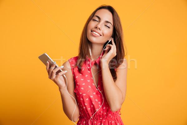 Pleased brunette woman in dress listening music on smartphone Stock photo © deandrobot