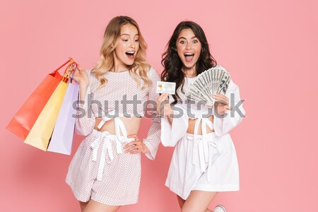 Two cheerful women holding packages on shoulders and showing peace Stock photo © deandrobot