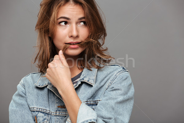 Close up portrait of a doubtful girl in denim jacket Stock photo © deandrobot