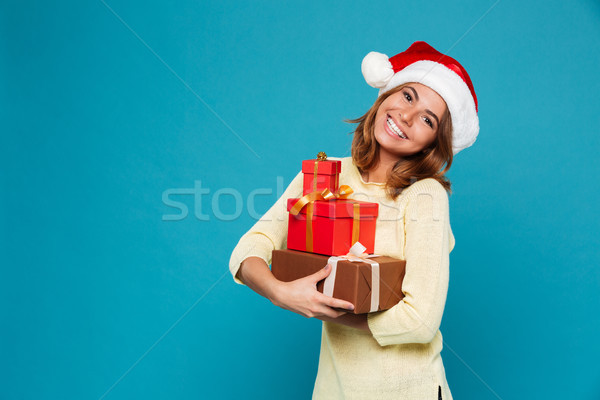 Smiling woman in sweater and christmas hat holding gift boxes Stock photo © deandrobot