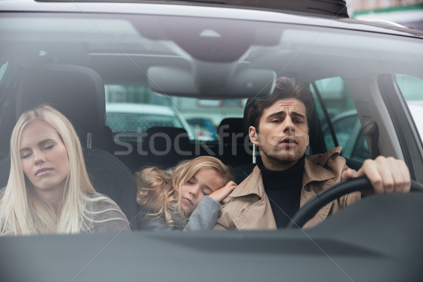 Concentrated man sitting in car with sleeping wife and daughter Stock photo © deandrobot