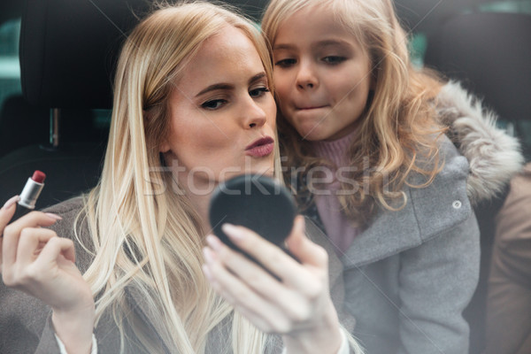Young pretty woman doing makeup look at mirror Stock photo © deandrobot