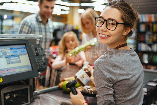 Happy cashier woman on workspace Stock photo © deandrobot