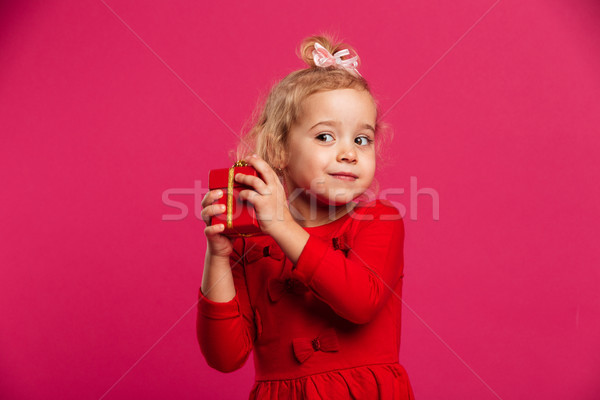 22554e97 Intrigued young blonde girl in red dress holding gift box Stock photo ©  deandrobot