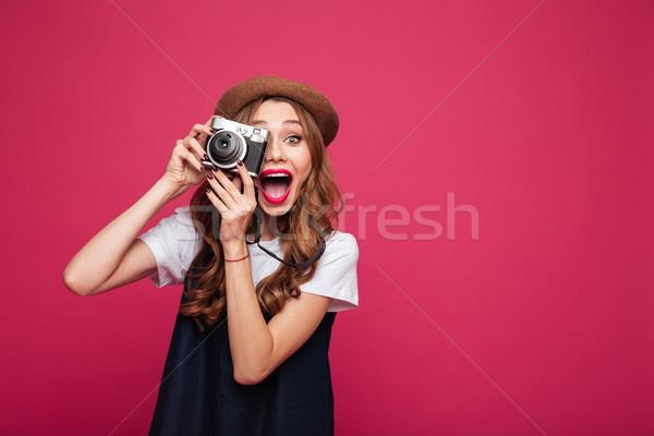Happy lady making photo with retro camera isolated Stock photo © deandrobot