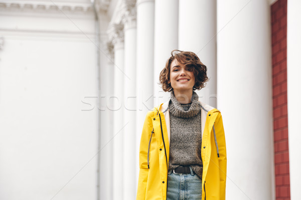 Smiling young woman dressed in raincoat Stock photo © deandrobot