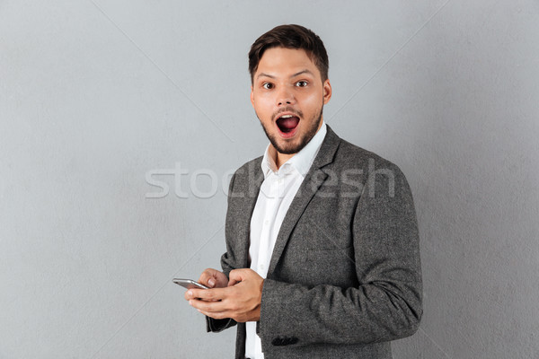 Portrait of an excited businessman holding mobile phone Stock photo © deandrobot