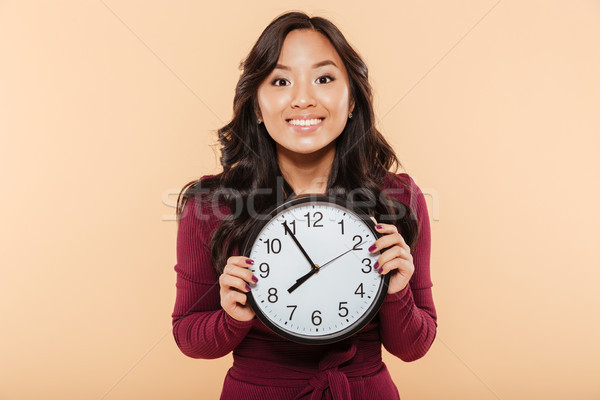 Happy emotions of asian woman with curly long hair holding clock Stock photo © deandrobot