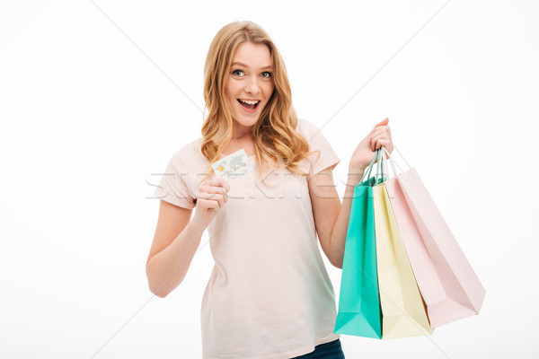 Cheerful young woman holding credit card and shopping bags. Stock photo © deandrobot