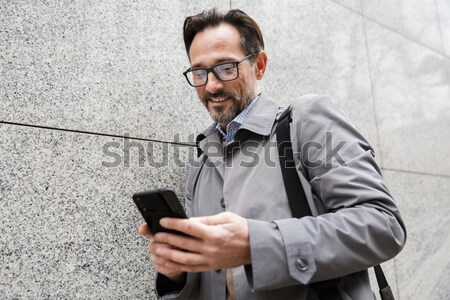 Portrait of a smiling bearded man texting on mobile phone Stock photo © deandrobot
