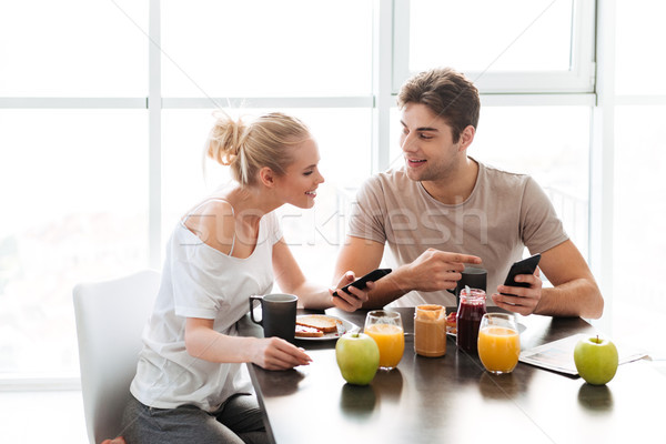 Young smiling man and woman talking with each other while have breakfast Stock photo © deandrobot