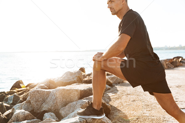 Cropped image of focused sportsman doing stretching Stock photo © deandrobot