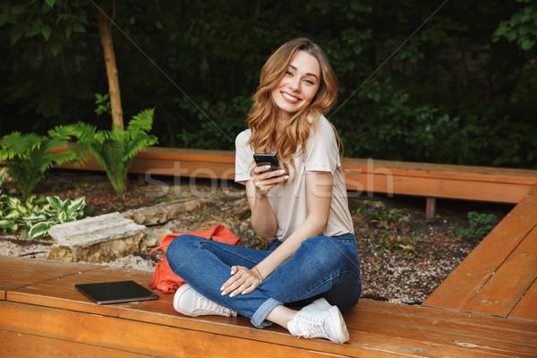 Elégedett fiatal lány mobiltelefon ül pad kint Stock fotó © deandrobot