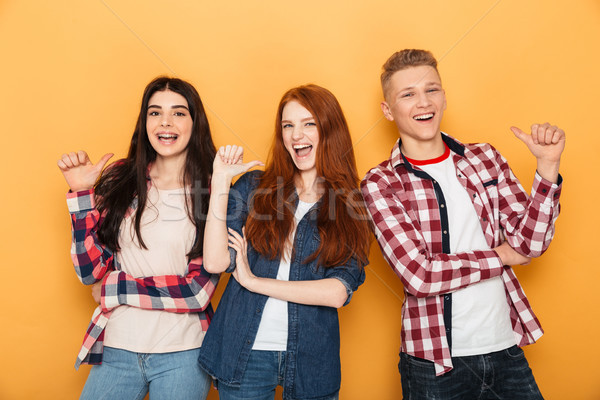 Group of happy school friends pointing fingers Stock photo © deandrobot