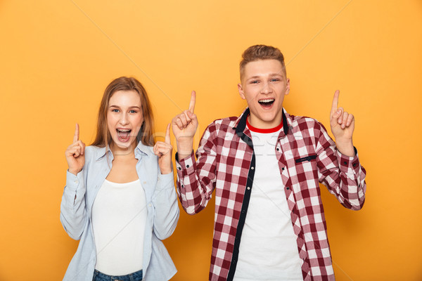 Stock photo: Portrait of a cheerful teenage couple pointing fingers up